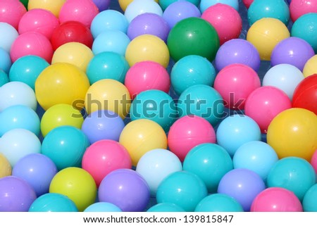Colorful plastic balls floating on water - stock photo