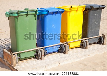 Colorful plastic containers in a row for separate garbage collection - stock photo