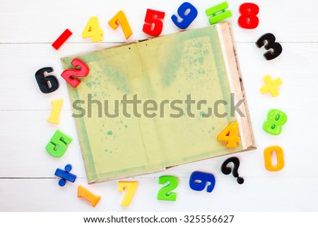 Colorful plastic numbers and open book with copy-space - stock photo