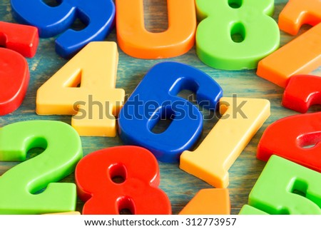 Colorful plastic numbers on a painted wooden background - stock photo