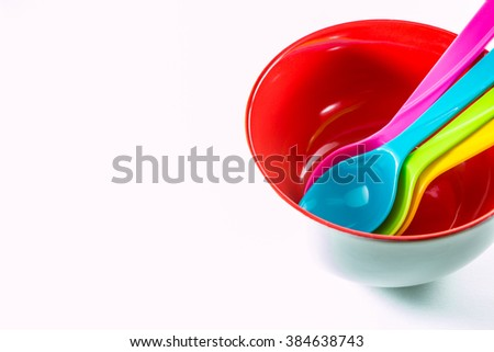 Colorful plastic spoons in red bowl on white background. - stock photo