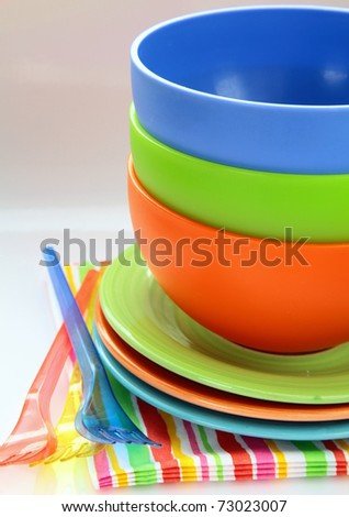 colorful plastic tableware  and napkins for picnics - stock photo