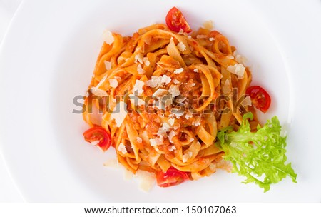Colorful plate of pasta bolognese with some fresh tomato, parmesan and green salad - stock photo