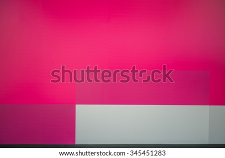 Colorful Plywood Wall.  Brightly painted plywood construction wall in tones of red, pink, magenta, and gray/grey, for use as an advertising backdrop - stock photo
