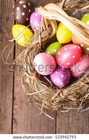 Colorful polka dot eggs in basket, Easter decorations - stock photo
