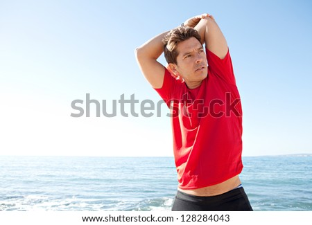 Colorful portrait of an attractive sports man stretching his arms and back while standing near the sea against a bright blue sky. - stock photo