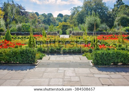 Colorful Public Flower Garden with Paths and Pond - stock photo