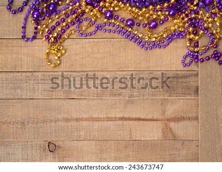 Colorful Purple and Gold Mardi Gras Beads on rustic wood board background with room or space for copy, text, your words.  Horizontal.  Louisiana State University school colors. - stock photo