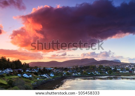 Colorful purple clouds at sunset  over a village - stock photo