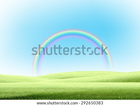 colorful rainbow with green grass lawn field over plain blue sky. Hope, happy, nature, natural idea template background - stock photo