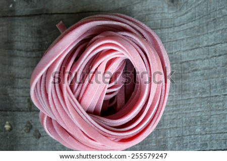 Colorful raw italian pasta on wooden background - stock photo