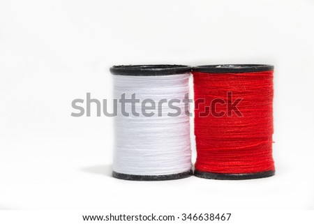 Colorful red and white thread isolated on white background - stock photo