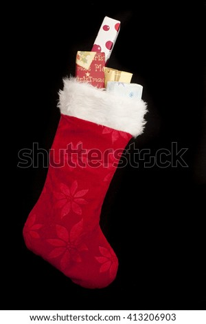 Colorful red Christmas stocking with decorative wrapped gifts peeking out the top over a black background with copy space - stock photo