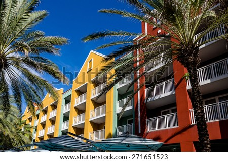 Colorful resort condos with palm trees and sun umbrellas - stock photo
