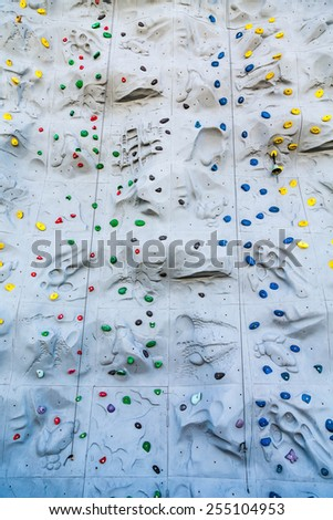 Colorful rock climbing wall with grips and ropes - stock photo