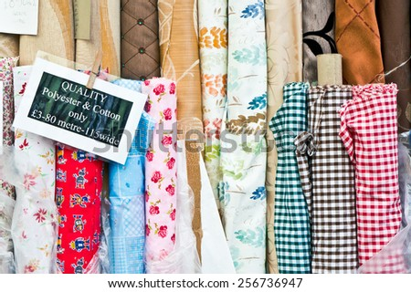 Colorful rolls of patterned fabric on sale at a market - stock photo
