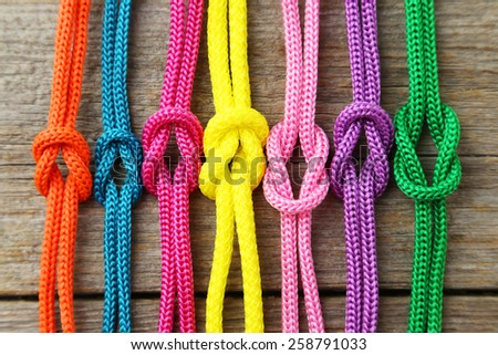 Colorful ropes on grey wooden background - stock photo