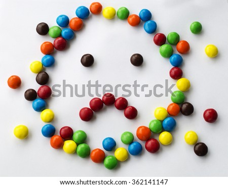 colorful sad, kind emotional candy face on white background made of round candies for children games looks like cartoon face - stock photo