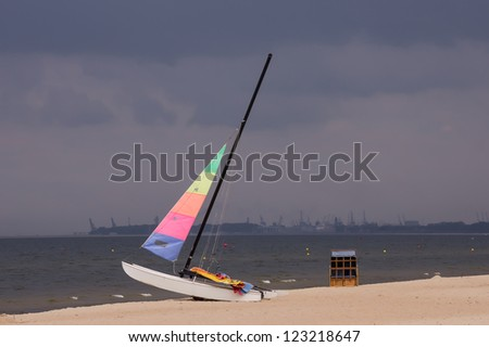 Colorful sailboat on the beach in Sopot, Poland, with the stormy clouds and Gdansk Shipyard in the background. - stock photo
