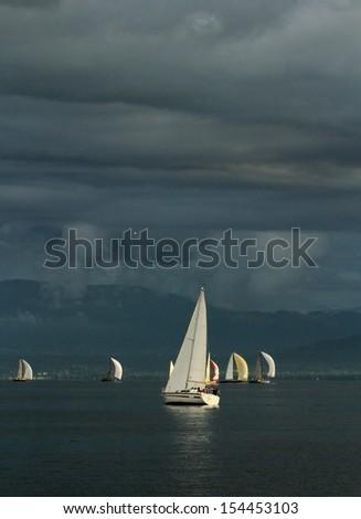 Colorful sailboat sailing on a calm evening with dramatic sunset, Geneva lake, Switzerland - stock photo