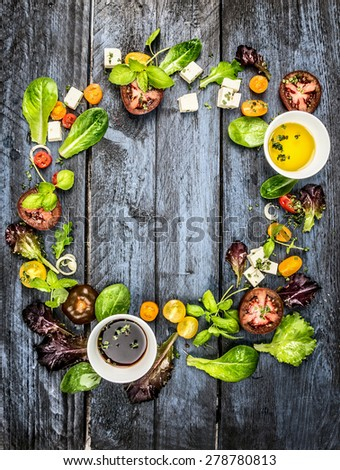 Colorful salad ingredients with tomatoes and feta cheese on rustic blue wooden background, round frame, top view - stock photo