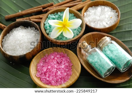 colorful salt in wooden bowl with cinnamon, frangipani ,salt in glass on banana leaf   - stock photo