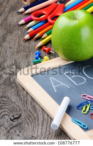 Colorful school supplies on wooden desk - stock photo