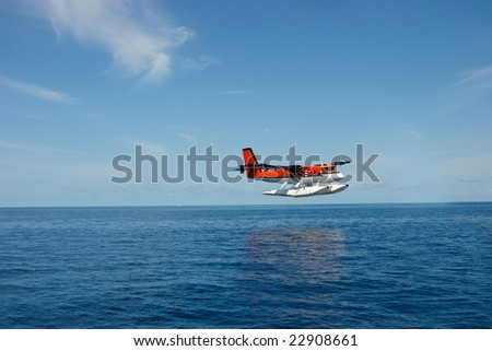 Colorful seaplane taking off water surface - stock photo