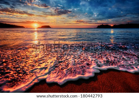 Colorful seaside beach sunrise with bright distant reflections - stock photo