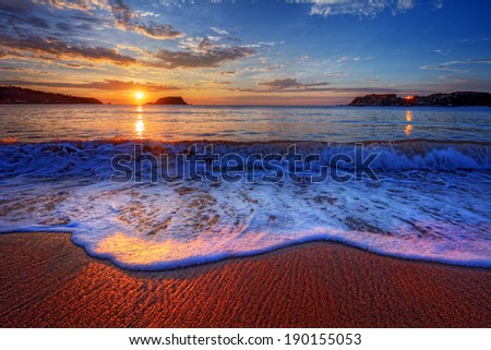 Colorful seaside beach sunrise with bright distant reflections 2 - stock photo