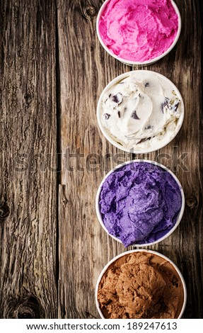 Colorful selection of Italian ice cream tubs viewed from above filled with delicious frozen dessert for a party or summer treat on an old wooden table with copyspace - stock photo