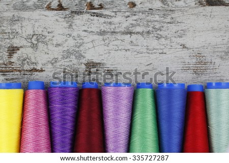 Colorful sewing coils in a wood background - stock photo