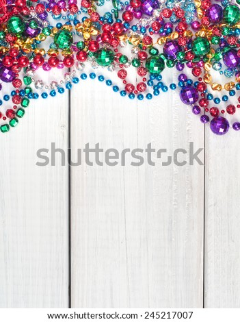 Colorful  Shiny Mardi Gras Beads on Rustic Painted White Board Background with room or space for copy, text, your words.  Vertical close up - stock photo