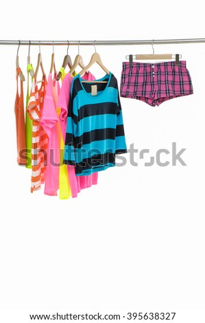 colorful shirts with pants on wooden hangers - stock photo