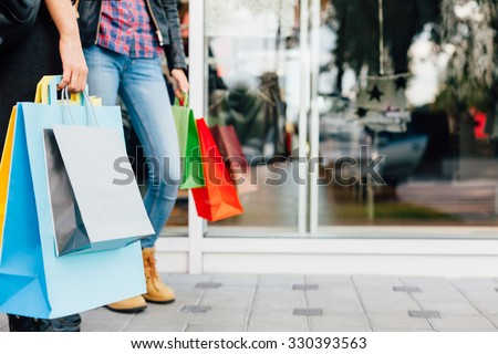 Colorful shopping bags in front of shopping windows - stock photo