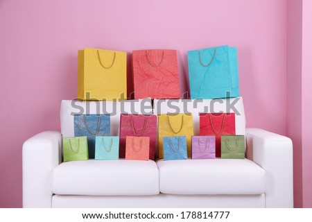 Colorful shopping bags on sofa, on color wall background - stock photo