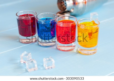 Colorful shot cocktails close up with ice cubes on light bar counter. - stock photo