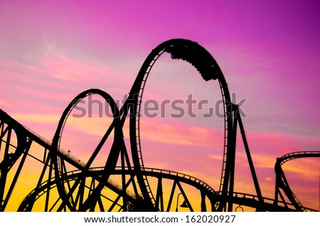 colorful silhouette of a roller coaster at sunset, after a sunny day at entertainment park - stock photo
