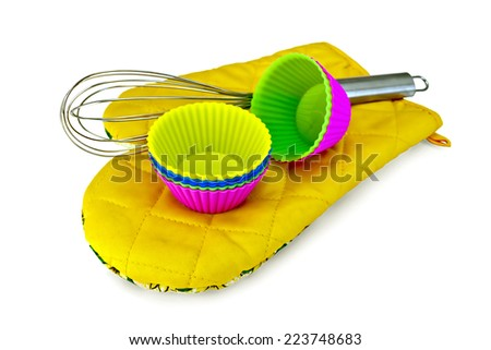 Colorful silicone molds for cakes, mixer on yellow cloth potholder isolated on white background  - stock photo