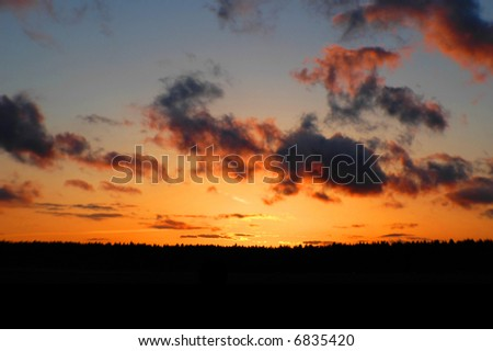 colorful sky at sunset with foreground silhouette - stock photo