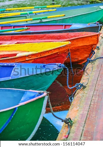 Colorful small boats parked to wooden pier. - stock photo