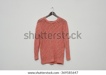 Colorful smart winter wear pink sweater on a hanger isolated on white wall background - stock photo