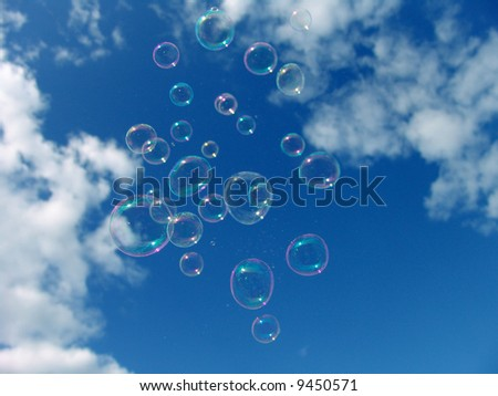 Colorful Soap Bubbles Against Blue Sky Background - stock photo