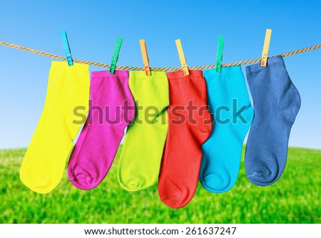 colorful socks hanging from a rope on the background of nature - stock photo