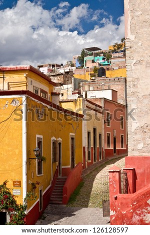 Colorful Spanish colonial houses stagger up a cobblestone street up a hillside in picturesque San Miguel de Allende, Mexico. - stock photo