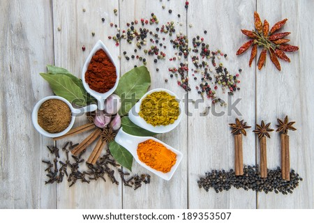 Colorful spices assortment on a wooden table in the kitchen - stock photo