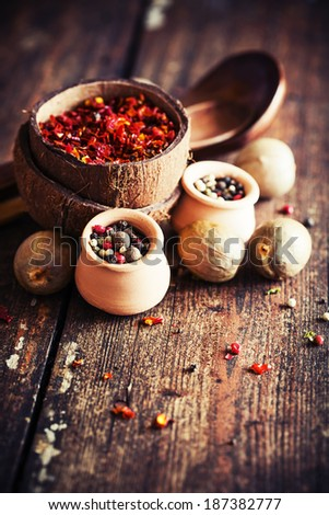 Colorful spices in bowls spilling onto an old aged scored wooden surface in a country rustic kitchen - stock photo