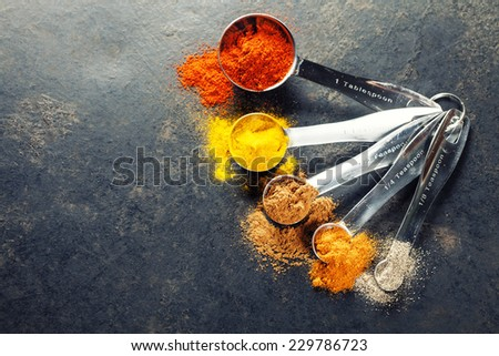 Colorful spices in metal spoons - beautiful kitchen image - stock photo