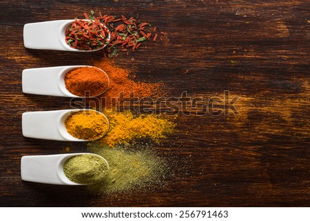 Colorful spices on brown wooden table top view - stock photo