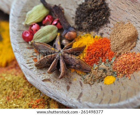 colorful spices with anise in a wooden spoon - stock photo